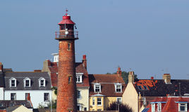 Old lighthouse amongst buildings. Royalty Free Stock Photo