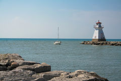 Old Lighthouse, boat entering harbor. Old working lighthouse on rock pier Lake Huron Royalty Free Stock Photos