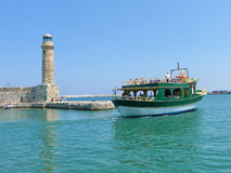 Old lighthouse and a boat in marina, Rethymno, Greece Stock Photos
