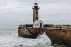 Old lighthouse and granite pier at the mouth of Douro river, Porto stock image