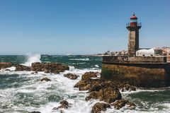 Old lighthouse and granite pier at the mouth of Douro river, Porto royalty free stock images