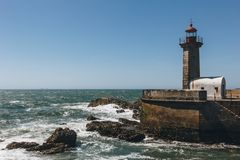 Old lighthouse and granite pier at the mouth of Douro river, Porto stock photos