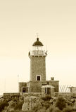 Old lighthouse on Greek island. Sepia view of old lighthouse on Greek island with sky background Royalty Free Stock Image