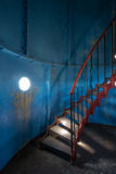 Old lighthouse on the inside. Red iron spiral stairs, round window and blue wall Stock Photo