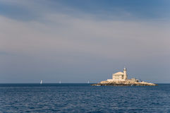 Old lighthouse on little island stock images
