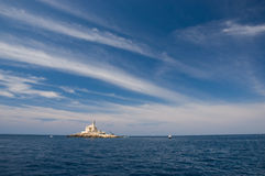 Old lighthouse on little island. Under beautiful sky royalty free stock photography