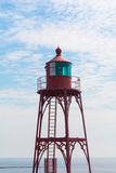 Old lighthouse at the North Sea, in Netherlands. Red old metallic lighthouse at the edge of the North Sea, under a serene sky, in Vlissingen, Zeeland Royalty Free Stock Photography