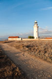 Old lighthouse of Paphos. Abandoned old lighthouse of Paphos in Cyprus with blue sky and rugged footpath Royalty Free Stock Photography