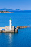 Old lighthouse on the pier, entrance to Propriano port. Corsica, France. White round tower made of stone with green top Stock Photos