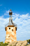 Old lighthouse on rock top on sky background Stock Images