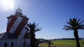 Old lighthouse and several palms Royalty Free Stock Photography