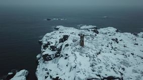 Old lighthouse. Shore Barents Sea. Kola Peninsula. Arctic Ocean winter landscape stock footage