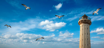 Old lighthouse in the sky with seagulls Stock Photos