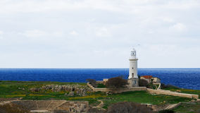 An old lighthouse stands over the sea and ruins. An old white lighthouse stands over the blue sea and ancient theatre ruins, in the middle of meadow coverd by stock image