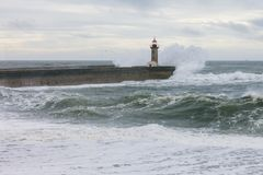 Old lighthouse in stormy sea waves Stock Photos