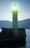 Old lighthouse tower silhouette with green light Stock Photos