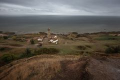Old Lighthouse under the rain storm sky clouds in autumn day. royalty free stock image