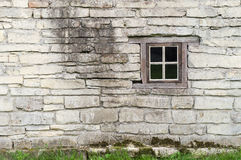 Old limestone wall with square window. Old limestone wall with square wooden window Royalty Free Stock Image