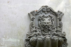 Old Lion Head Fountain, which is mounted on a white-gray wall. Which is not used for a long time. Do leaves covered. See the whole garden. copy space Stock Image