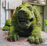 Old lion sculpture covered of green moss in Ubud monkey forest, Bali, Indonesia stock images