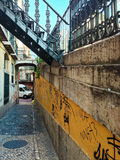 Old Lisbon alley. With graffited wall and steelwaork handrail and staircase. Vertical Royalty Free Stock Photo