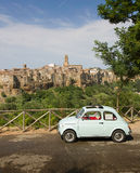 Old little car, green valley and medieval city, Italy Stock Photo