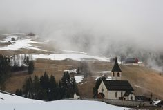 Old little church in the mountains. Old alpine little church in the mountains with snow and fog Stock Image