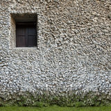 Old little window on a wall. White stone. Building. A old window on a wall of a building constructed with small white stones. At the bottom of the green moss Stock Photography