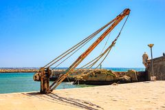 Old loading crane in the harbor.  Royalty Free Stock Photography