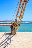 Old loading crane in the harbor.  Royalty Free Stock Images