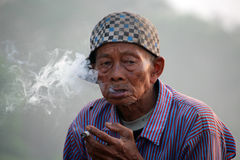 Old local indonesian man smoking in Java Stock Photography