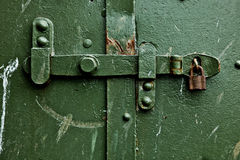 Old lock. Hasp and lock from an old wartime bunker, rust showing through the green paint Royalty Free Stock Photo