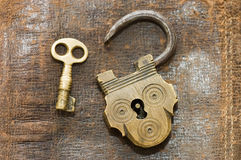 The old lock and key on a leather background Stock Photos
