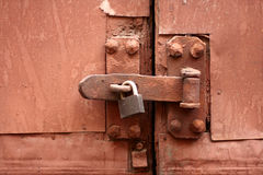 Old lock, latch and rusty gate. Old padlock, latch and rusty gate coloured rick-red royalty free stock photo