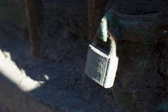 Old lock. A weathered antique lock patina secure on an old wrought iron gate Stock Image