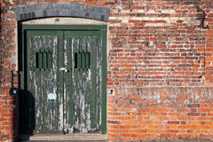 Old locked dock side doors. Sitting in a badly repaired wall. Double doors with window bars for security and peeling green paint Stock Photos