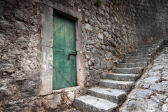 Old locked green door and stone stairway. In Perast town, Montenegro Stock Images