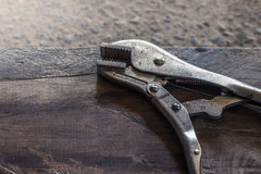 Old locking pliers on the wood floor. - Stock Image Stock Photos