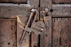 Old locks on an antique wooden door. Special metal locks in retro style on the old strong door of thick planks Royalty Free Stock Photos