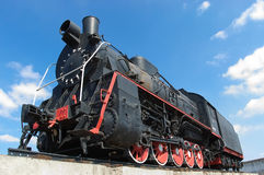 Old locomotive. Old black locomotive on background blue sky Stock Photography