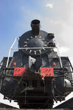Old locomotive frontal. Old black locomotive on background blue sky Royalty Free Stock Photography