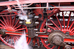 Old Locomotive Wheels. Steam gushing out near the red wheels of an old locomotive stock photos
