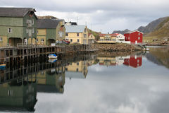 Old lofts mirroring in  the harbour of Nyksund Stock Image