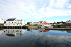 Old Lofts mirroring in  Henningsvaer's harbour Royalty Free Stock Image