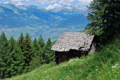 Old log cabin in the alps. This is a piece of a farm where we keep the grain and fodder for livestock. This one is old and abandoned Stock Photography