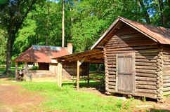 Old Log Cabin Sheds Shack. Couple of rustic old log cabin sheds with large oak trees and pine trees in the background Royalty Free Stock Images