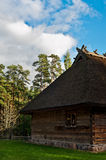 Old log cabin in the wooded forest of evergreen trees. Open-air ethnography museum near Riga, Latvia Royalty Free Stock Photos