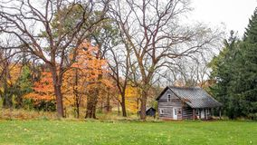 Old Log Home in Wisconsin Woods in Fall. An old fashioned log home in the Wisconsin woods in the fall with orange, yellow and green trees royalty free stock images