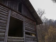 Old log house abandoned in the mountains stock photo