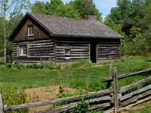 Old log house with yard and fence. Stock Image